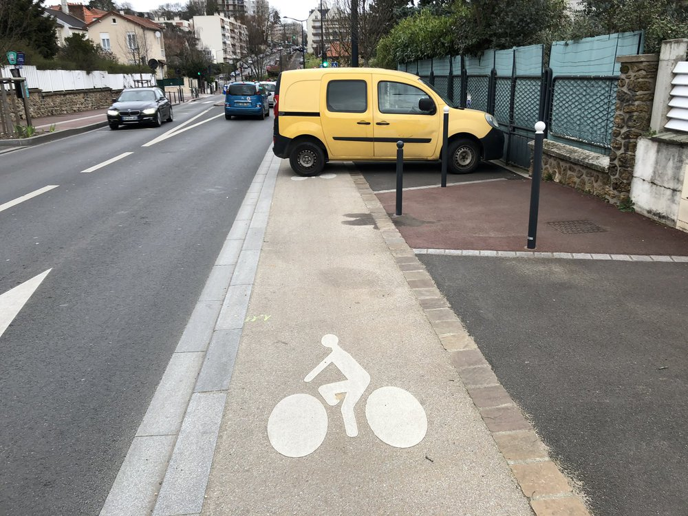Une voiture bloquant la piste cyclable avenue Jean Moulin, mettant en danger les cyclistes qui doivent se déporter d'urgence.